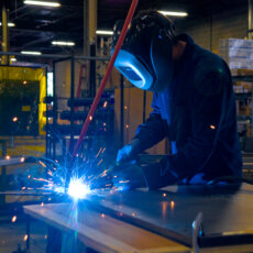 A Matot worker welds a metal component to be used in a dumbwaiter.