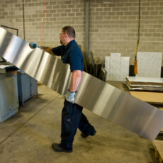 A Matot shop worker carries a sheet of metal to be used on a new dumbwaiter.