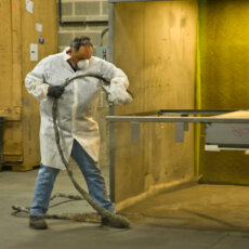 A Matot worker sprays part of a dumbwaiter with a finishing solution.