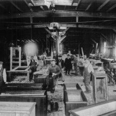 The original Matot shop, with workers working on building wooden dumbwaiters, shown in black and white.